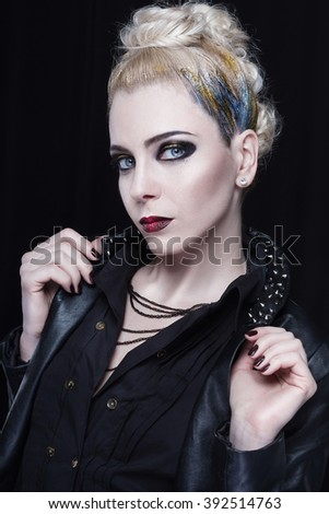 Young attractive blonde woman in a leather jacket with spikes. She is rebellious, she has a creative blue and yellow mohawk and heavy makeup. - stock photo