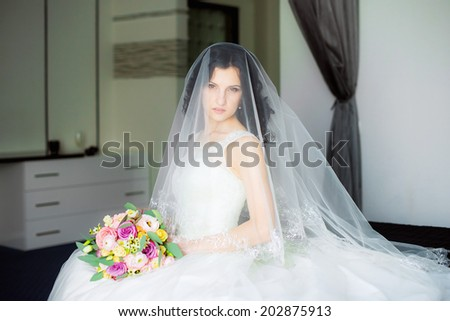 Young attractive bride with flowers wedding bouquet waiting for the groom  - stock photo
