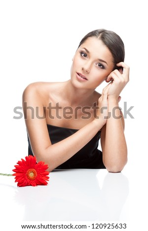young attractive brown-eyed brunette caucasian female with pink gerbera flower in her dark hair which gently smiling and soft looking at camera and softly touching her cheek with her hand - stock photo