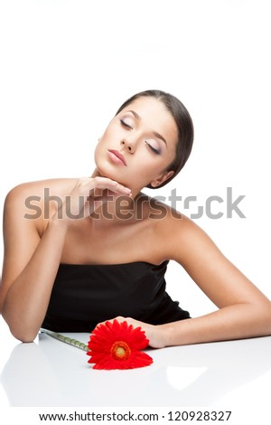 young attractive brown-eyed brunette caucasian female with red gerbera flower on the desk which gently closed her eyes and softly touching her face with her hand isolated on white background - stock photo