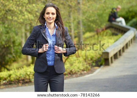 young attractive brunette businesswoman in park, wear blue shirt and grey suit, outdoor shoot - stock photo