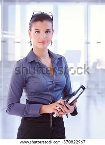 Young attractive brunette caucasian secretary standing at business office with personal organizer, looking at camera, smiling. Woman suit, copyspace. - stock photo