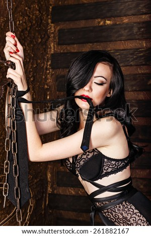 Young attractive brunette with bright makeup and sword belt in black lace underwear, bra and panties maxi, hands tied tie. Holds the tip of the tie in the teeth. The concept of BDSM and bondage. - stock photo