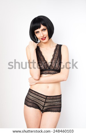 young attractive brunette woman in black lingerie  on white background - stock photo