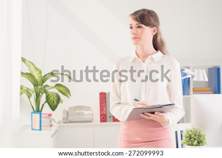 Young attractive business lady with a folder - stock photo