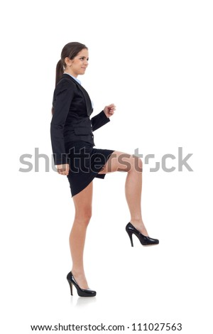 Young attractive business woman stepping on imaginary step. Isolated on white. - stock photo