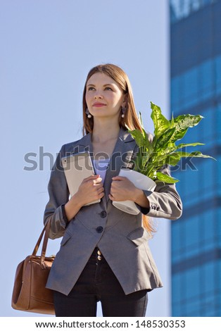 young attractive business women with flower, bag and pad outdoors, looking away,  on building blurred background - stock photo
