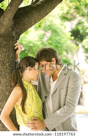 Young attractive businessman and businesswoman having a romance while hugging under a tree in the city. - stock photo