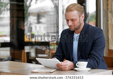 Young attractive businessman having lunch and working in a cafe - stock photo