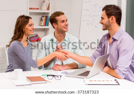 Young attractive businessman in casual clothes and beautiful businesswoman shaking their hands and smiling while working in office. Another attractive businessman smiling and supporting. - stock photo