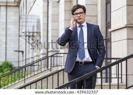 Young attractive businessman in suit having mobile phone conversation with beautiful architecture in the background - stock photo