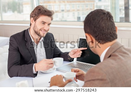 Young attractive businessman is sitting at the table and communicating with his customer. He is pointing his finger at the notebook and smiling. The men are drinking coffee - stock photo