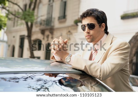 Young attractive businessman leaning on the top of a car in a classic street, wearing sunglasses. - stock photo
