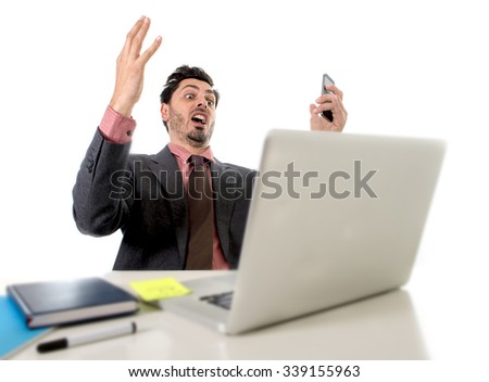 young attractive businessman sitting at office desk working stressed on computer laptop talking on mobile phone overworked looking worried in work stress and  business concept - stock photo