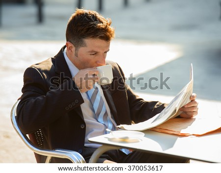 young attractive businessman sitting outdoors having coffee cup for breakfast early morning reading newspaper news looking relaxed and concentrated in business people concept - stock photo