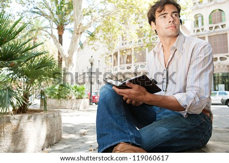 Young attractive businessman using a hands free device to make a call on his cell phone while sitting on a bench in a city square with classic architecture. - stock photo