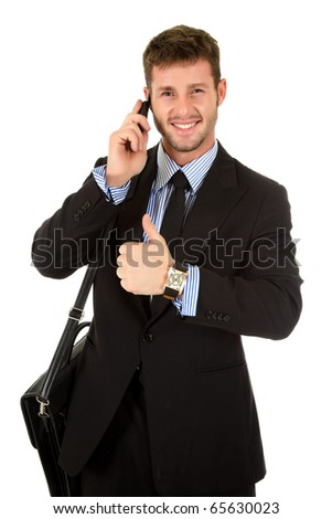 Young attractive businessman with briefcase and talking on mobile phone, and showing thumb up. Studio shot. White background. - stock photo