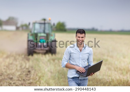 Young attractive businessman with laptop standing in front of tractor with trailers on harvested field - stock photo