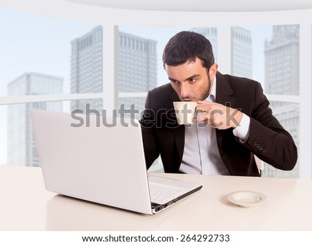 young attractive businessman working at business district office sitting at computer desk drinking coffee satisfied and relaxed looking at laptop screen in successful career concept  - stock photo