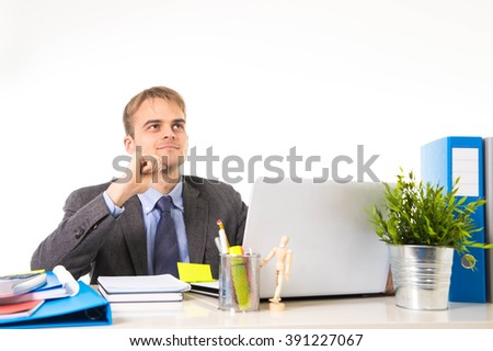young attractive businessman working busy with laptop computer holding pen thoughtful smiling and thinking at office desk in business project success concept isolated on white - stock photo