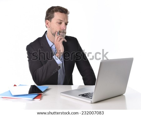 young attractive businessman working in stress at office desk computer laptop looking reflexive and doubtful, pensive and thoughtful isolated on white background - stock photo