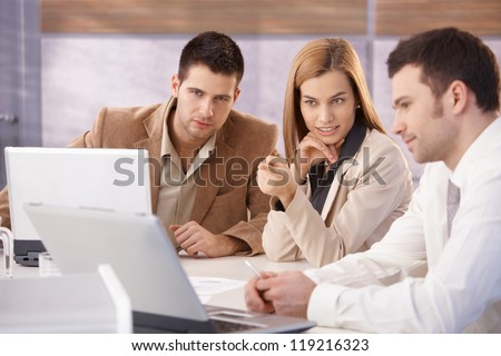 Young attractive businesspeople teamworking in meeting room. - stock photo