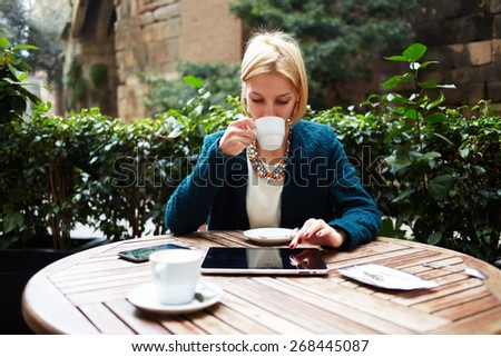 Young attractive businesswoman at coffee time working on digital tablet while sitting on the terrace of coffee shop, caucasian blond well dressed woman using touch pad while sitting in coffee shop - stock photo