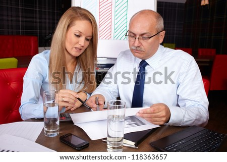 Young attractive businesswoman discuss with senior businessman, background in the office - stock photo