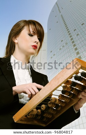 Young attractive businesswoman holding wooden abacus over city background. - stock photo