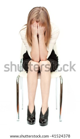 Young attractive businesswoman in shirt and skirt sitting on white chair with hands over face. Isolated on white - stock photo