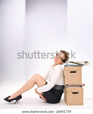 Young attractive businesswoman next to pile of documents, lots of copy space - stock photo
