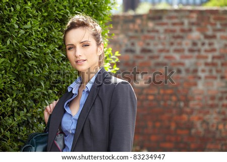 young attractive businesswoman, outdoor shoot,blurred red brick wall as background, can be used as copy space - stock photo