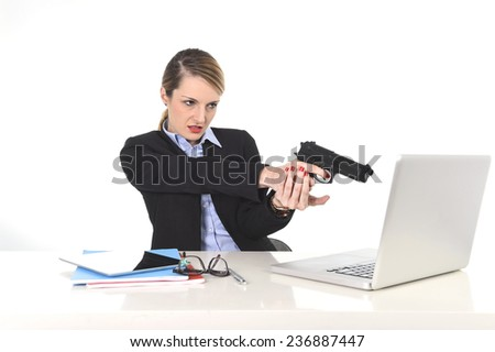 young attractive businesswoman pointing gun to computer laptop sitting at office desk desperate and stressed having problems with work project and technology isolated on white background - stock photo