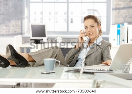 Young attractive businesswoman sitting at desk, legs on top of desk, talking on phone, smiling. - stock photo