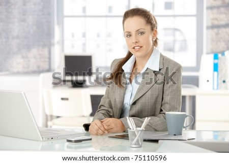 Young attractive businesswoman sitting by desk in office, having laptop.? - stock photo