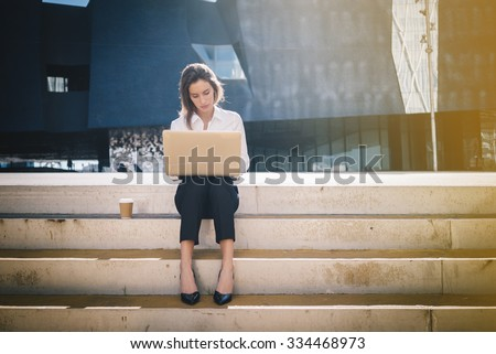 Young attractive businesswoman sitting on the stairs and using modern laptop - stock photo
