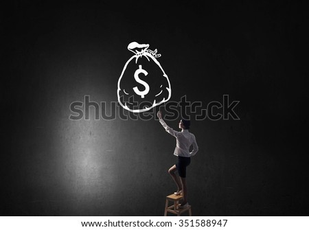 Young attractive businesswoman standing on chair and reaching money bag - stock photo