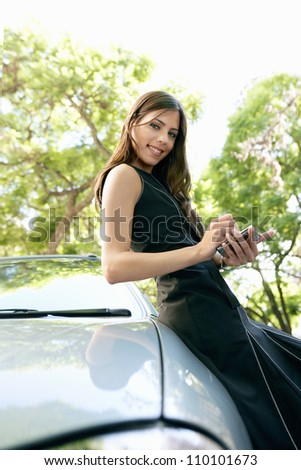Young attractive businesswoman using a smart phone while leaning on a shiny car in a tree lined street. - stock photo