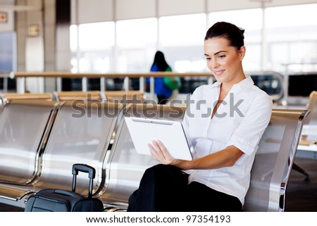 young attractive businesswoman using tablet computer at airport - stock photo