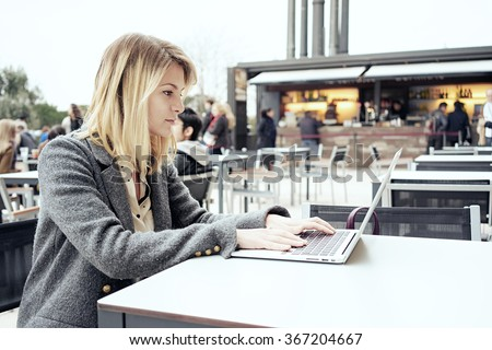 young attractive businesswoman with blonde hair working in a coffee-shop outside with laptop computer - stock photo