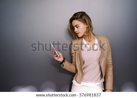 young attractive businesswoman with blonde hair writes a text message on a gray background with copy space area for your text o design. - stock photo