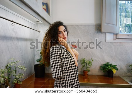 Young attractive businesswoman with long curly hair talking on cell telephone.brunette Caucasian girl talking on smart-phone in coffee-shop - stock photo