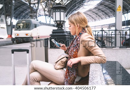 young attractive businesswoman writes a text message while waiting for the train. attractive young blonde woman using smart-phone while sitting on the railway station platform - stock photo