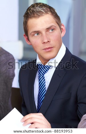 Young attractive, busy looking businessman, wears white shirt and blue necktie - stock photo