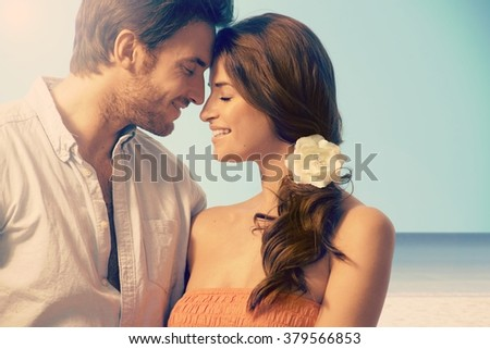 Young attractive casual caucasian married couple having a romantic moment at the seascape beach. Eyes closed, touching, love, romance, flower in hair. - stock photo