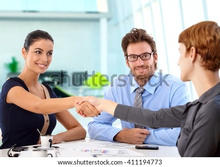 Young, attractive caucasian business people shaking hands on a successful deal at office meeting. Sitting at table, smiling. - stock photo