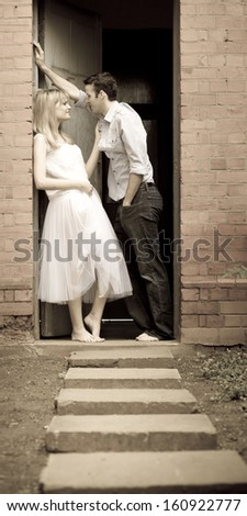 Young attractive caucasian couple leaning against door frame flirting - stock photo