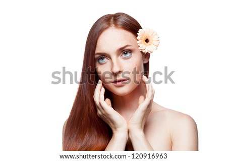 young attractive caucasian female with beige flower in her gorgeous long natural straight red hair which and soft looking out the camera and softly touching her cheek with her hands isolated on white - stock photo