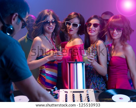 young attractive caucasian girls dancing and having fun at a party with sunglasses and cocktails in their hands in front of a dj mixing music with turntables - stock photo