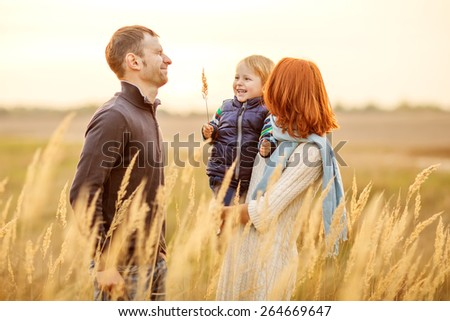 Young attractive caucasian parents and their child have fun outdoor on sunny day - stock photo